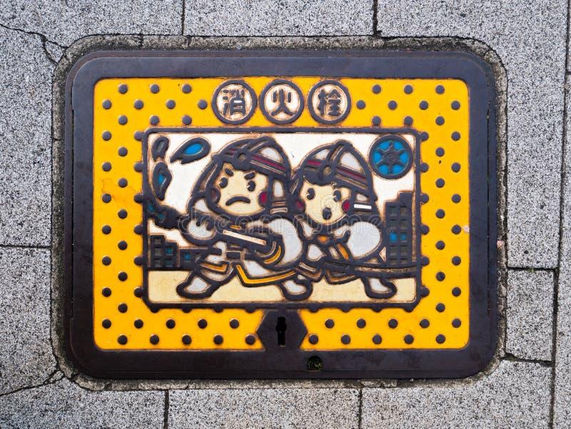 Tampa de câmara de visita colorida da boca de incêndio de fogo no Tóquio, Japão fotografia de stock