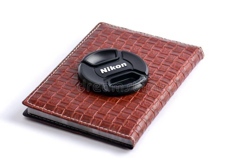 Tampa de lente de Nikon no caderno de couro imagens de stock royalty free