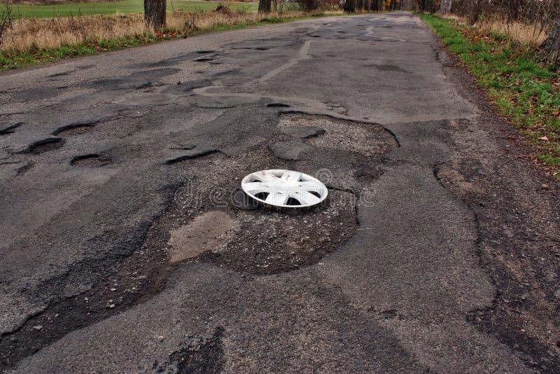Tampa de roda grampeada na estrada danificada fotografia de stock royalty free