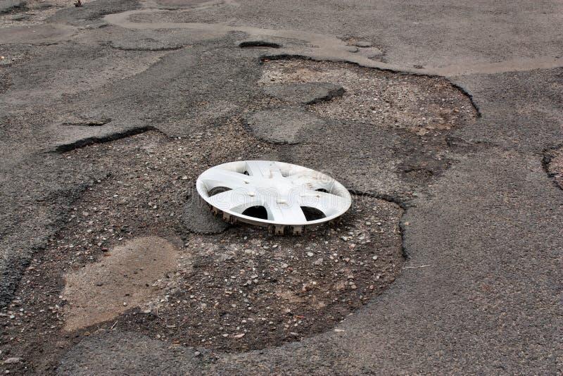 Tampa de roda grampeada na estrada danificada imagem de stock