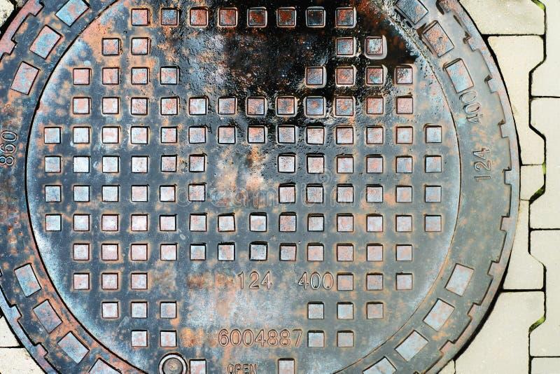 Tampa do dreno do metal no pavimento fotografia de stock royalty free