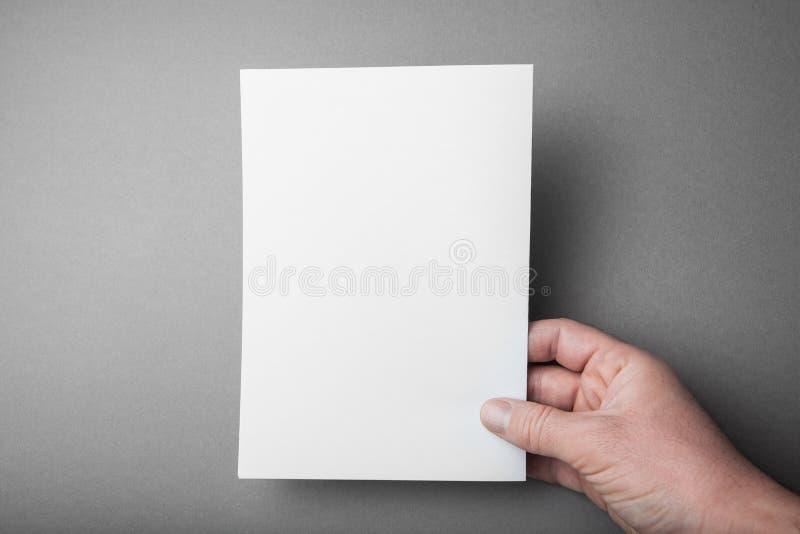 Tampa do folheto em um fundo cinzento, um modelo na mão de um homem europeu fotos de stock royalty free
