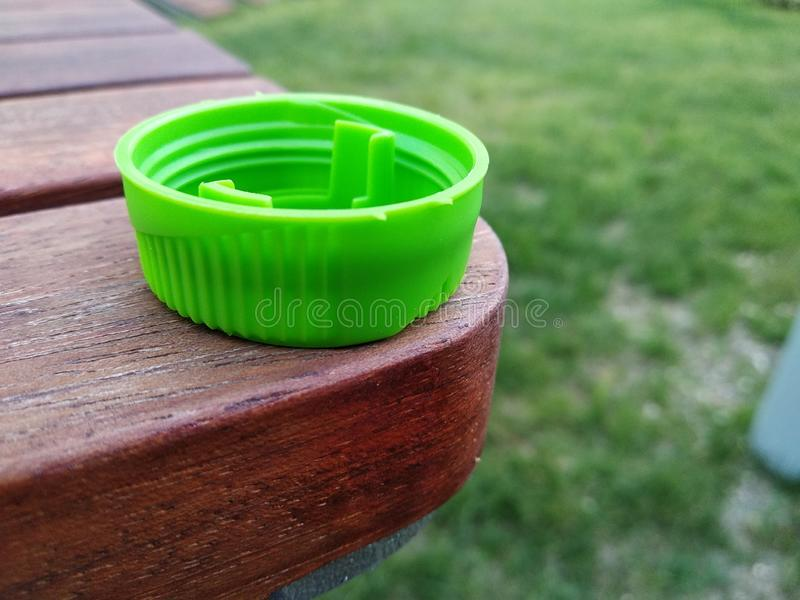 A tampa verde está na tabela de madeira reciclagem plástica, cuidados médicos, cuidado do planeta recycling uso de utensílios de  imagem de stock