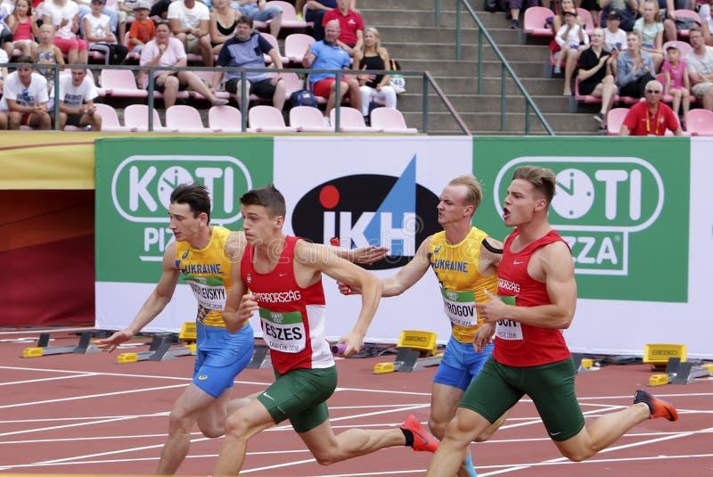 Oleksandr PYROHOV, Andriy VASYLEVSKYY form Ukraine, Dániel ESZES, Milán PISCH from Hungary 4X100 metres relay IAAF World U20. TAMPERE, FINLAND, July 13 royalty free stock photo