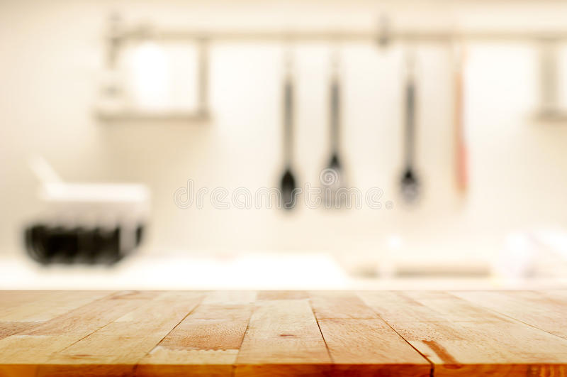 Tampo da mesa de madeira (como a ilha de cozinha) no fundo da cozinha do borrão imagem de stock