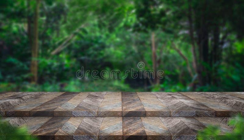 Tampo da mesa de madeira do grunge vazio da etapa com a árvore do borrão na frente tropical imagens de stock