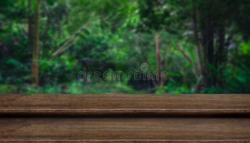 Tampo da mesa de madeira escuro do grunge vazio da etapa com a árvore do borrão em tropical fotos de stock