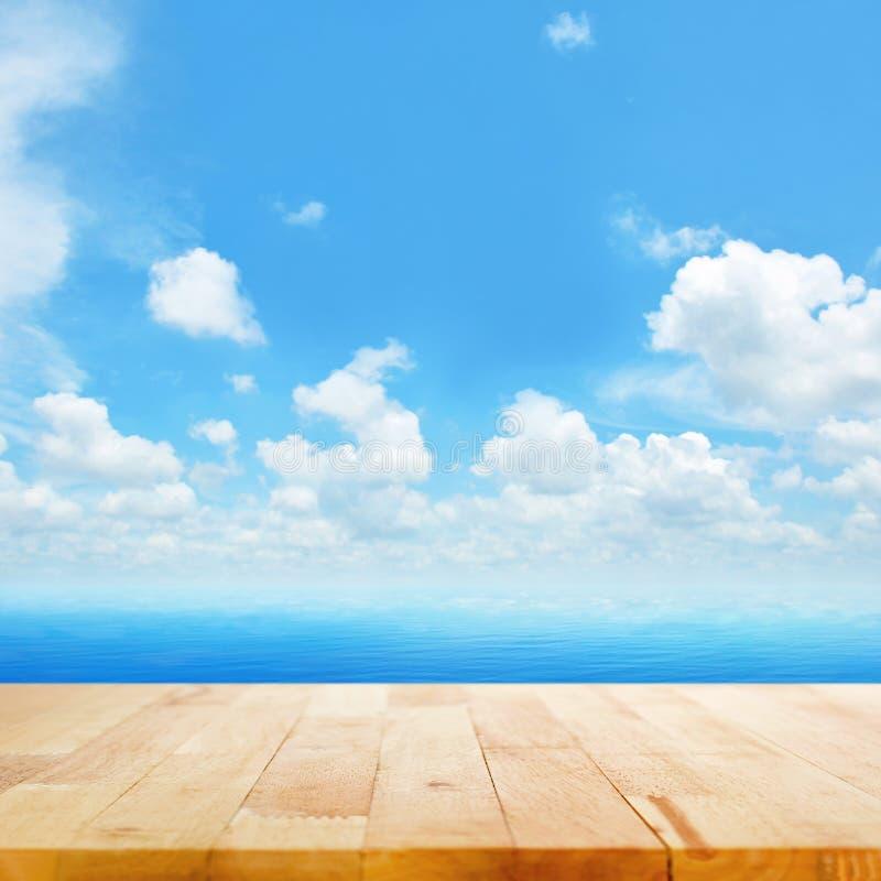 Tampo da mesa de madeira na água do mar azul e no fundo brilhante do céu do verão fotos de stock