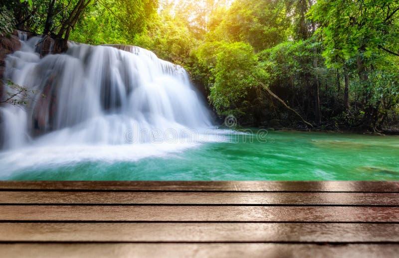 Tampo da mesa de madeira na cachoeira fantástica na floresta tropical fotos de stock