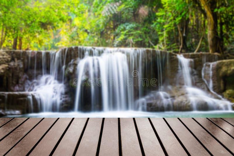 Tampo da mesa de madeira na floresta profunda borrada da cachoeira fotos de stock royalty free