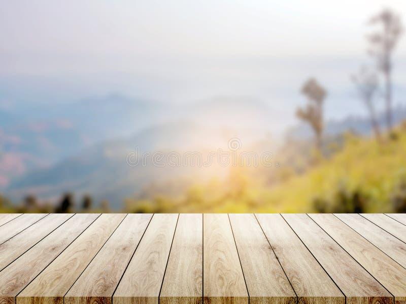 Tampo da mesa de madeira na montanha do monte do borrão um fundo da natureza do nascer do sol imagem de stock