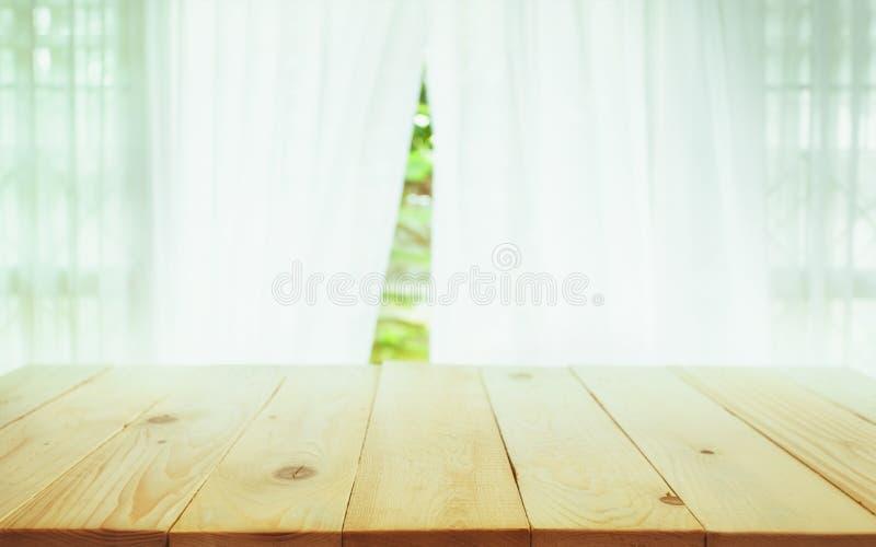 Tampo da mesa de madeira no borrão da cortina com verde da opinião da janela do tr imagem de stock
