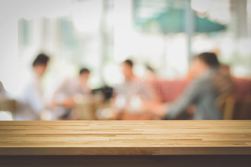 Tampo da mesa de madeira no fundo do borrão dos povos na cafetaria foto de stock royalty free