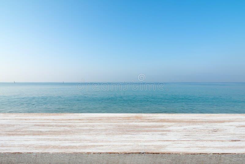 Tampo da mesa de madeira no mar azul borrado e no backgrou branco da praia da areia fotos de stock royalty free