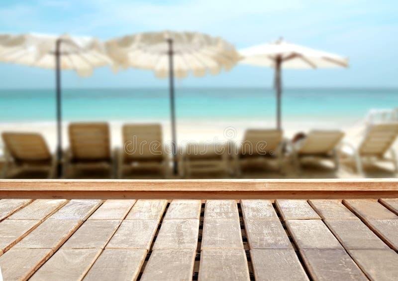 Tampo da mesa de madeira no mar azul borrado e no fundo branco da praia da areia foto de stock royalty free