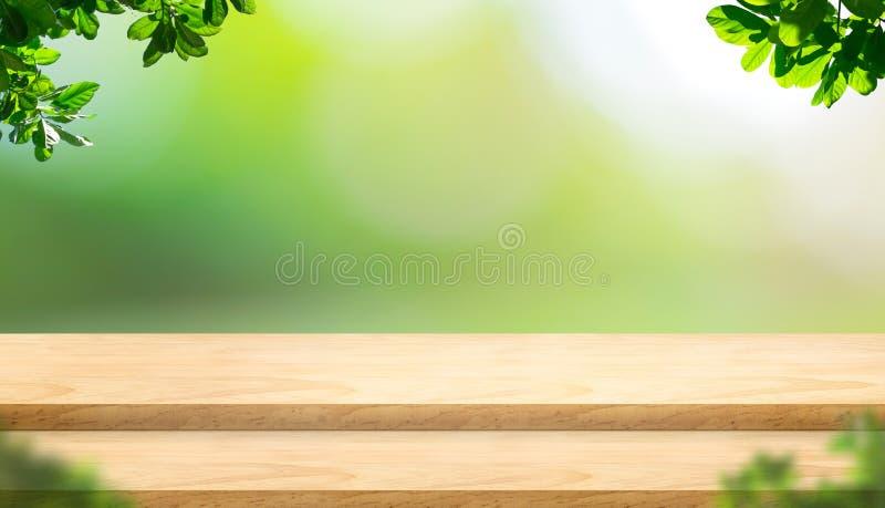 Tampo da mesa de madeira da prancha vazia da etapa com a árvore do borrão no parque com boke fotos de stock