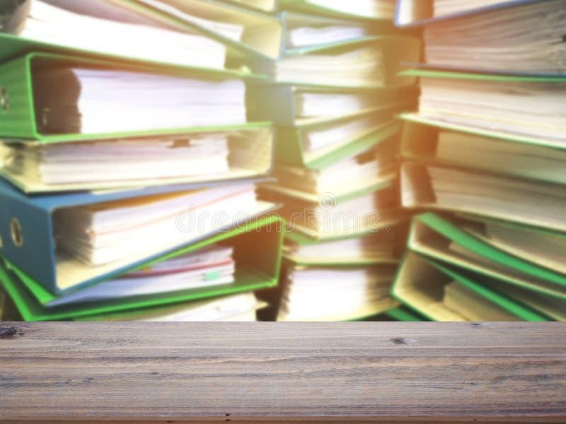 Tampo da mesa de madeira sobre a pilha do arquivo no fundo do escritório foto de stock