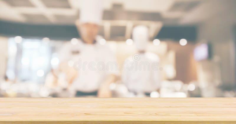 Tampo da mesa de madeira vazio com o cozinheiro chefe que cozinha no fundo borrado cozinha do restaurante fotos de stock