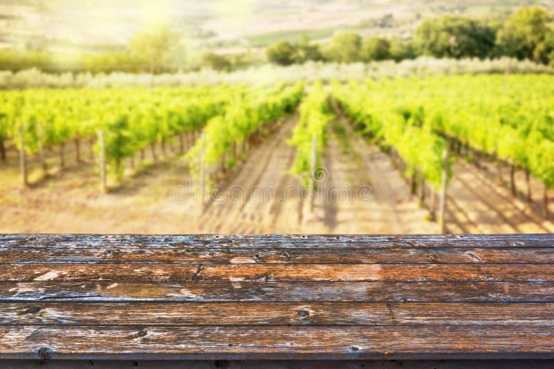 Tampo da mesa de madeira vazio, fundo ensolarado do vinhedo, pronto para uso para a exposição de seus produtos imagem de stock royalty free