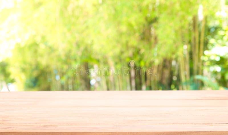 Tampo da mesa de madeira vazio no fundo verde natural do sumário do borrão fotos de stock royalty free