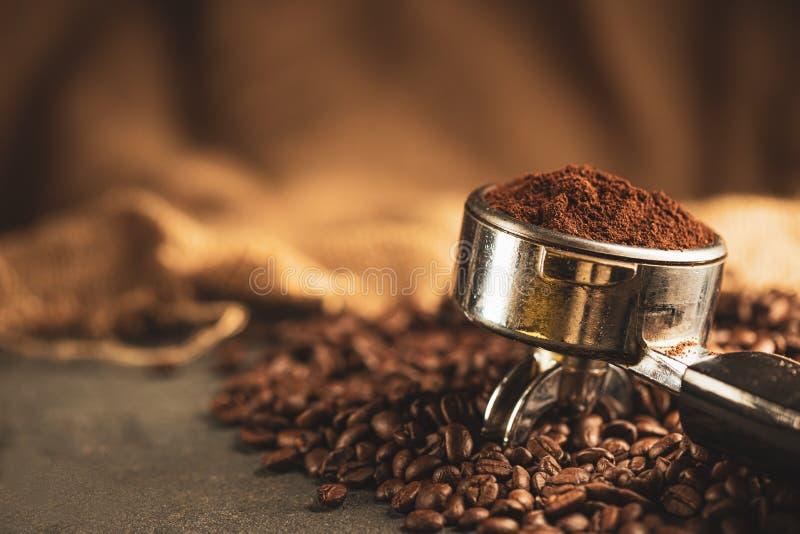 Tampon de café, presse-café en acier inoxydable et haricots de café rôtis du grille-café sur fond noir, falsificateur d'outil photo libre de droits