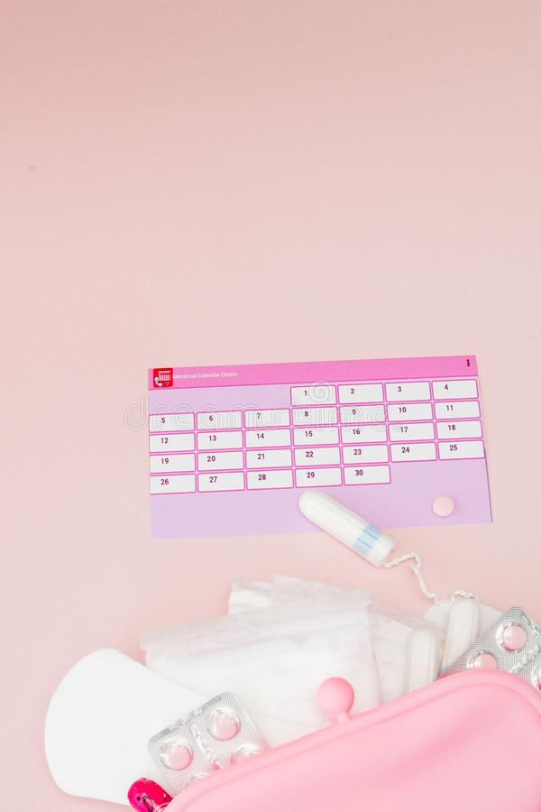 Tampon, feminine, sanitary pads for critical days, feminine calendar, pain pills during menstruation on a pink background. royalty free stock image