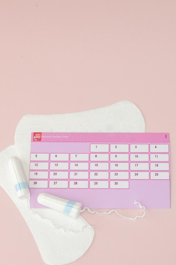 Tampon, feminine, sanitary pads for critical days, feminine calendar, pain pills during menstruation on a pink background. stock photo