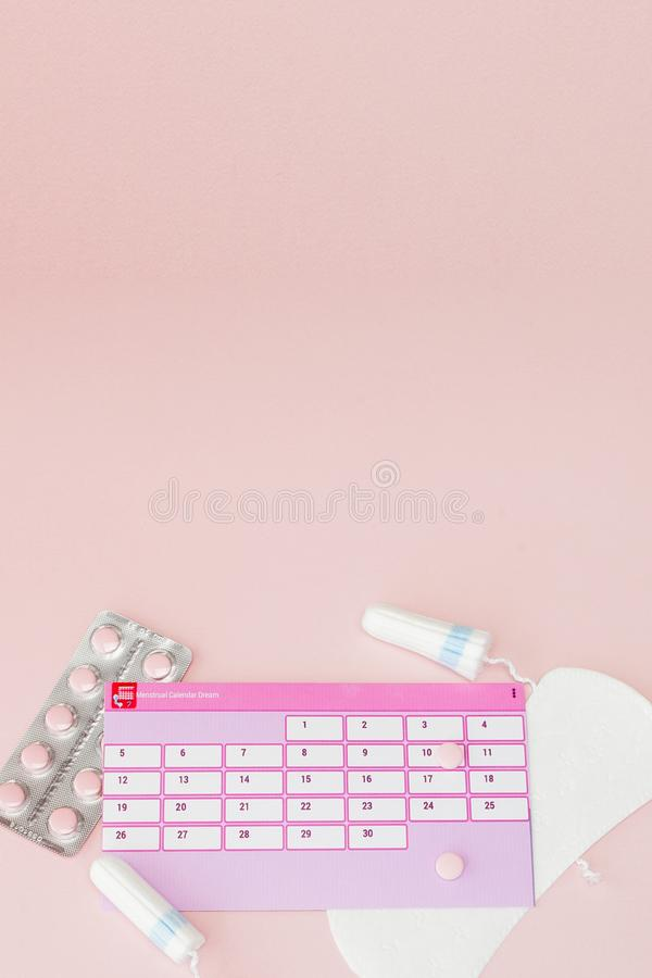 Tampon, feminine, sanitary pads for critical days, feminine calendar, pain pills during menstruation on a pink background. stock images