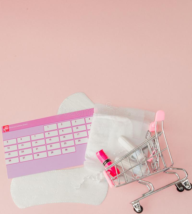 Tampon, feminine, sanitary pads for critical days, feminine calendar, pain pills during menstruation on a pink background. royalty free stock images