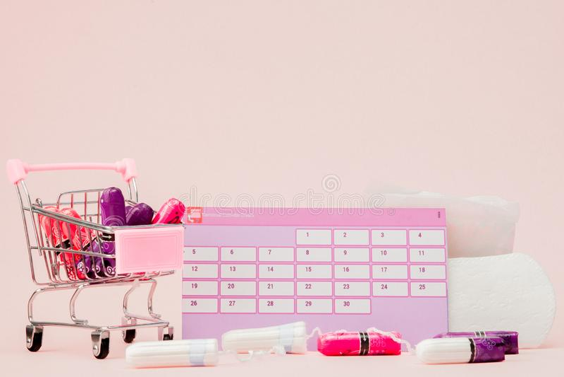 Tampon, feminine, sanitary pads for critical days, feminine calendar, pain pills during menstruation on a pink background. stock photos