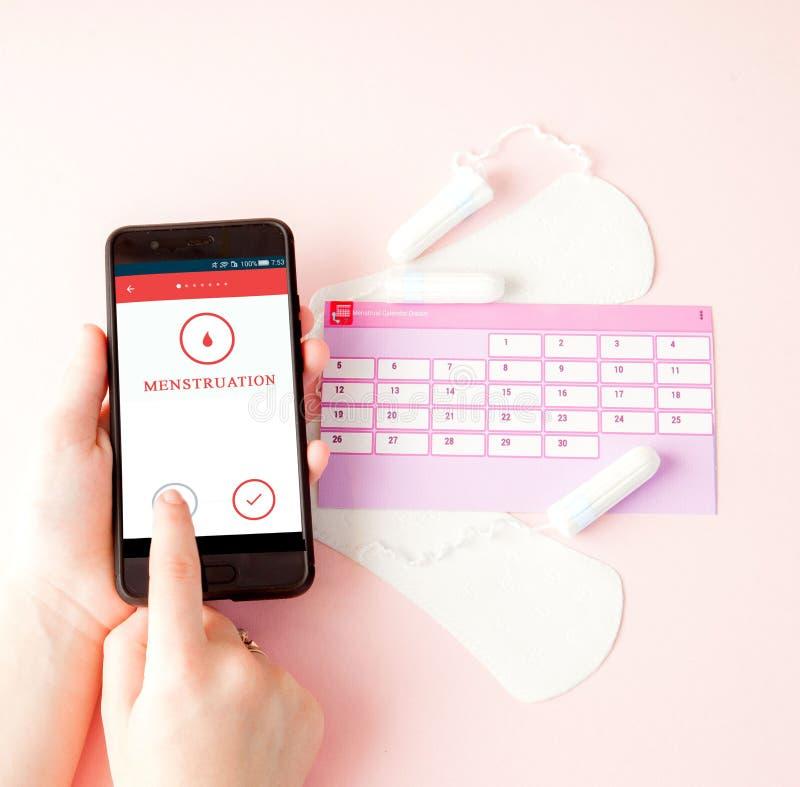 Tampon, vrouwelijke, sanitaire stootkussens voor kritieke dagen, vrouwelijke kalender, pijnpillen tijdens menstruatie op een roze royalty-vrije stock foto