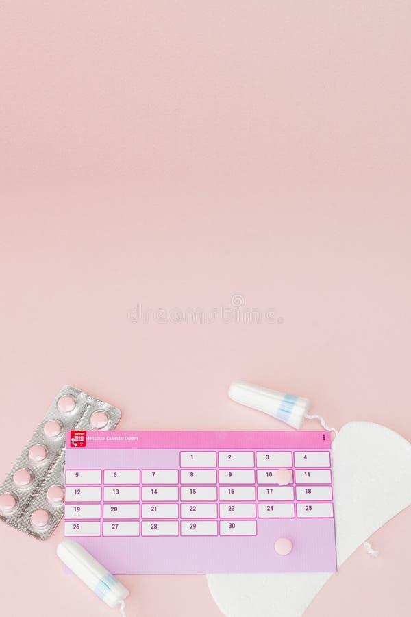 Tampon, vrouwelijke, sanitaire stootkussens voor kritieke dagen, vrouwelijke kalender, pijnpillen tijdens menstruatie op een roze stock afbeeldingen