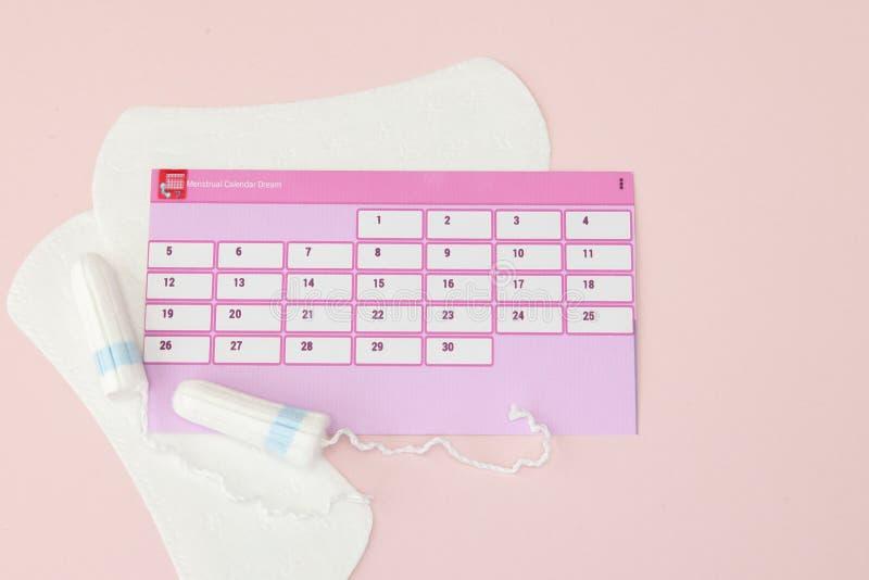 Tampon, vrouwelijke, sanitaire stootkussens voor kritieke dagen, vrouwelijke kalender, pijnpillen tijdens menstruatie op een roze stock foto's