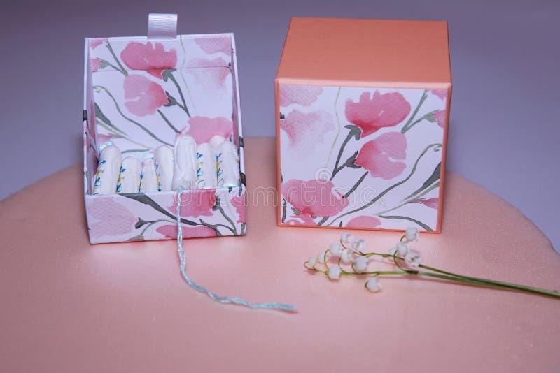 Tamponi bianchi puliti del cotone in una scatola di tamponi su fondo rosa menstruation Igiene femminile nei periodi, trattamento immagini stock libere da diritti