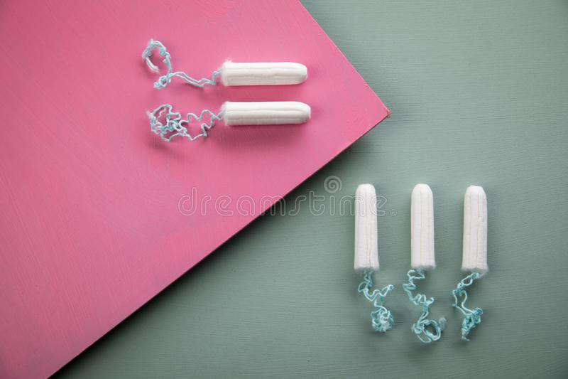 Tampons on green mint and rose pink background for female personal hygiene and protection during menstruation period cycle royalty free stock photos