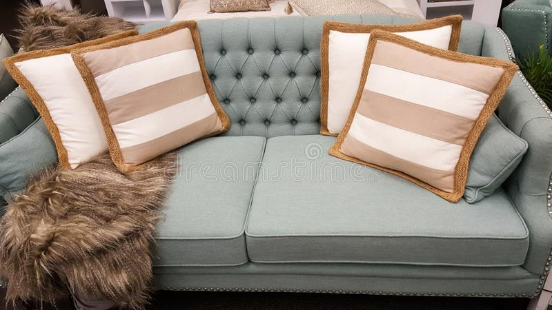 Tan en witte kussens op een bank zoals die door binnenlandse ontwerper wordt gestileerd stock foto