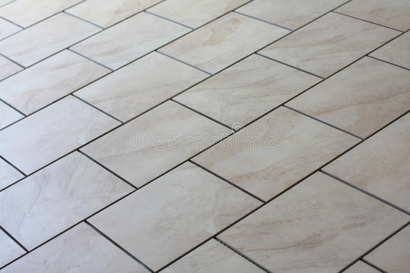 Tan floor tiles. Beige or tan colored porcelain tiles are being installed on a concrete floor