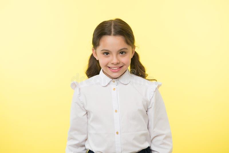 Tan lindo Fondo alegre sonriente del amarillo de la cara del uniforme escolar de la muchacha El niño listo de nuevo a extremo de  imagenes de archivo