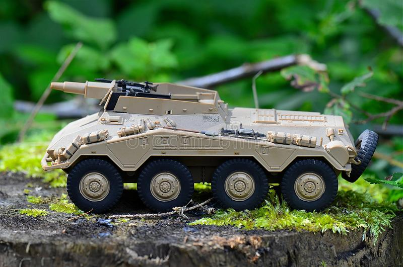 Tan Military Artillery Vehicle Toy on Wood Stump royalty free stock photography