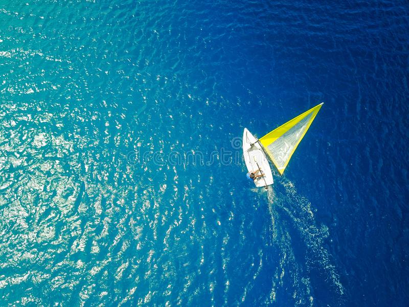 Overhead view of a laser sailboat in warm tropical waters stock photos