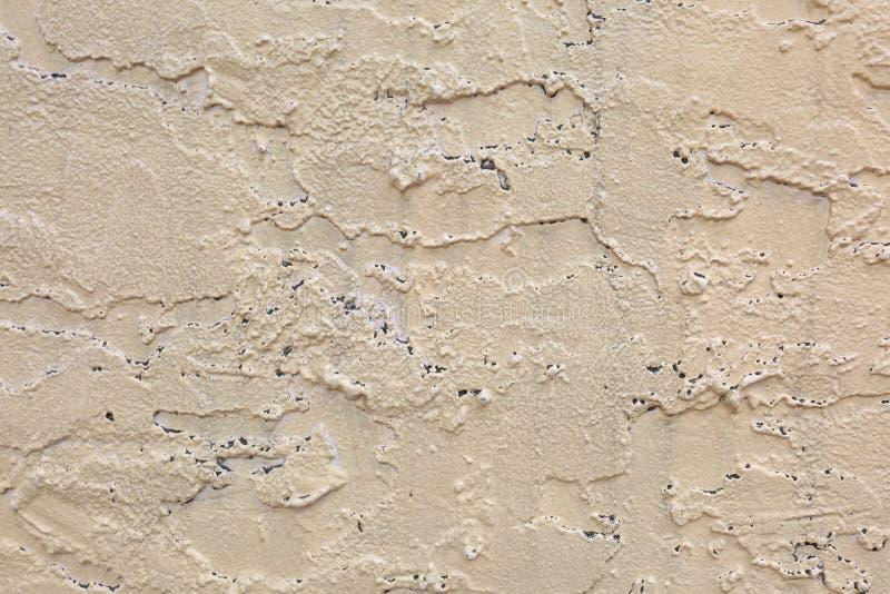 Tan Wall esteriore con struttura approssimativa dei fori e dello stucco immagini stock libere da diritti