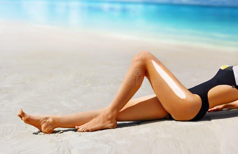 Tan Woman Applying Sunscreen on Legs. Solar cream sun protection concept.  stock images