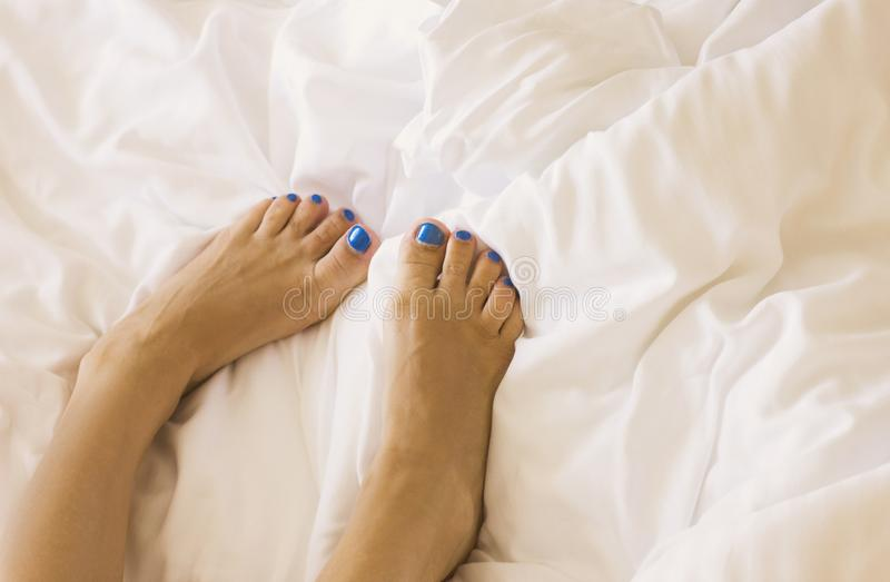 Women`s feet with blue pedicure on white bedding stock photo