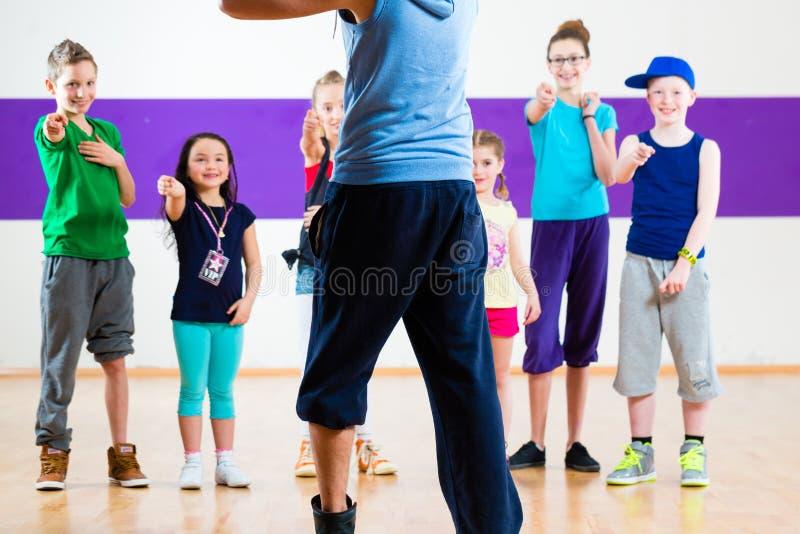 Tana nauczyciel daje dzieciakom sprawności fizycznej klasie obraz royalty free