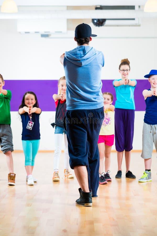 Tana nauczyciel daje dzieciakom Zumba sprawności fizycznej klasie fotografia royalty free