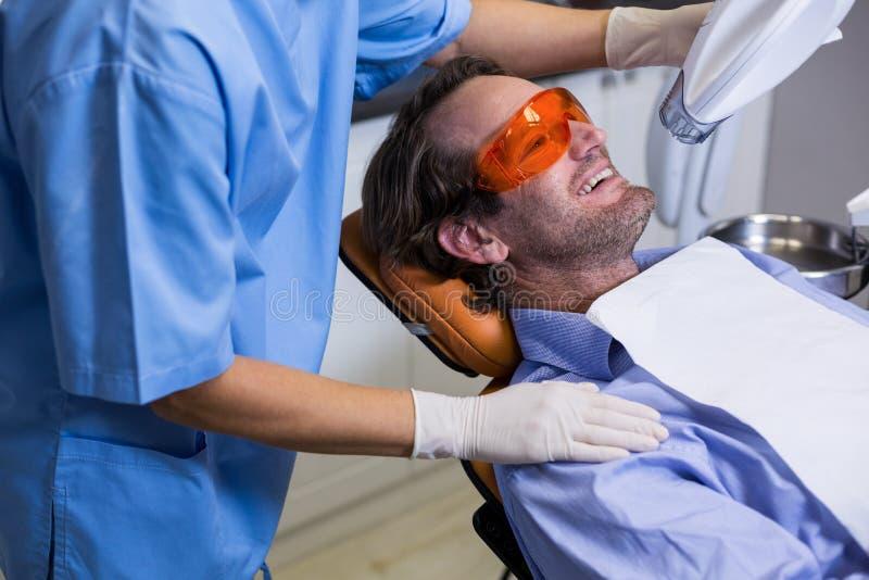 Tand- assistent som undersöker den unga tålmodiga munnen arkivfoto