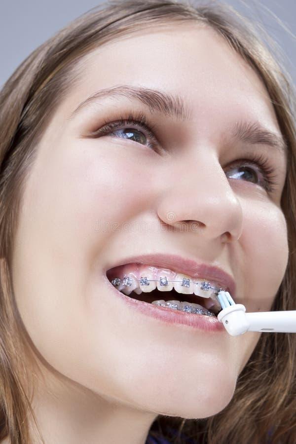Tand- begrepp och idéer Extrem Closeupstående av den Caucasian tonårs- flickan som borstar tänder arkivbild
