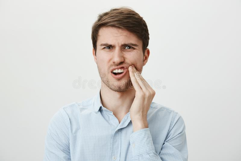 Tand en gezondheidsconcept Portret van gehinderde aantrekkelijke Europese modelholdingshand op tand, de oorzaak van de gevoelspij royalty-vrije stock fotografie