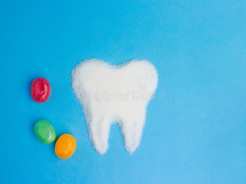 Tand från socker med godisar på blå bakgrund, symbol arkivfoton