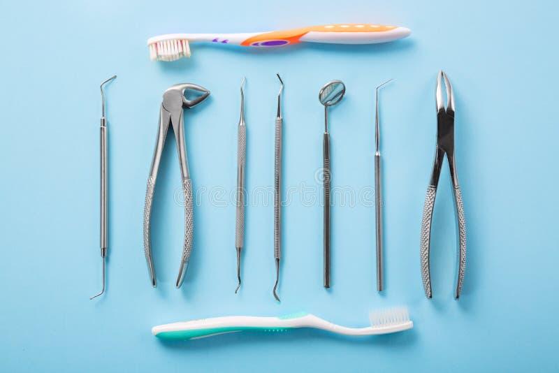 Tand- hälso- och teethcarebegrepp Bästa sikt av den tand- hjälpmedeluppsättningen på blå bakgrund med tandborstar i tandläkarekli royaltyfri foto